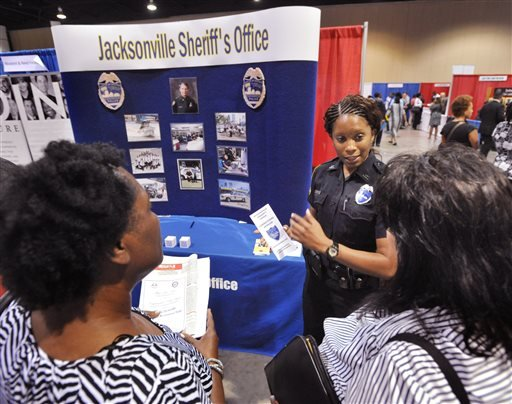 In this June 16, 2014 photo, Jacksonville police officer F. D. Williams, center, talks to job seekers during the City-Wide Job & Resource Fair at the Prime Osborn Convention Center in Jacksonville, Fla.