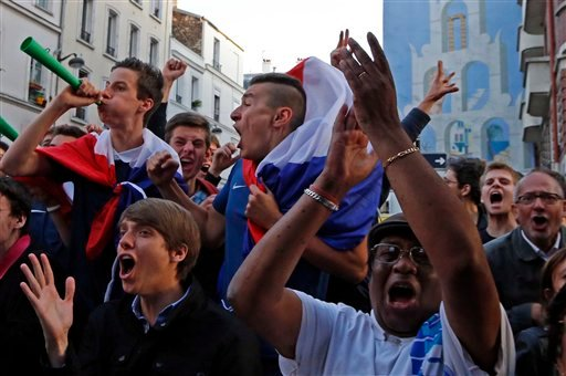 French soccer supporters react after the first goal as they watch a live broadcast of the group E World Cup soccer match between Switzerland and France, in the Metro 14th District bar in Paris, France, Friday, June 20, 2014.