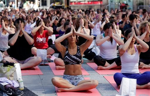 Thousands of New Yorkers are marking the first day of summer by practicing yoga in Times Square, during the 12th annual Solstice in Times Square, sponsored by the Times Square Alliance and Athleta, Gap Inc.'s exercise-wear brand, Saturday, June 21, 2014.