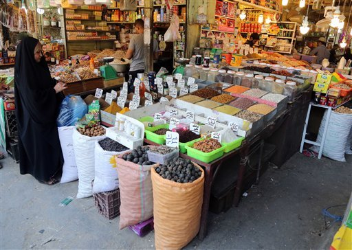 In this photo taken on June 17, 2014, an Iraqi woman buys food at a market in Baghdad, Iraq.
