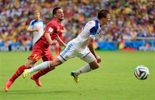 Russia's Maksim Kanunnikov is tripped by Belgium's Dries Mertens (14) during the group H World Cup soccer match between Belgium and Russia at the Maracana Stadium in Rio de Janeiro, Brazil, Sunday, June 22, 2014. (AP Photo/Bernat Armangue)