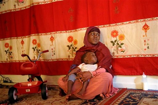 In this June 5, 2014 photo, Somali refugee Hasna Abdi, 26, holds her child Muridi Hassan, 1, as he falls asleep after a bottle feeding in the main room of their apartment in Springfield, Mass.