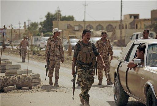 Oct. 6, 2010, file photo: armed Sunni militiamen work at a checkpoint in Samarra, 60 miles (95 kilometers) north of Baghdad, Iraq. (AP Photo/Maya Alleruzzo, File)