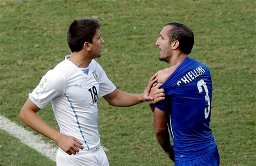 Italy's Giorgio Chiellini (3) complains after Uruguay's Luis Suarez ran into his shoulder with his teeth during the group D World Cup soccer match between Italy and Uruguay at the Arena das Dunas in Natal, Brazil June 24, 2014. (AP Photo/Hassan Ammar)