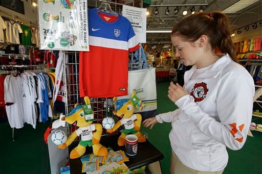 Employee Darcy Aders adjusts World Cup items that are for sale at Soccer Village, Wednesday, June 25, 2014, in Cincinnati. (AP Photo/Al Behrman)