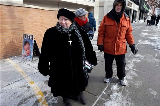 This Dec. 17, 2013 file photo shows anti-abortion protester Eleanor McCullen, of Boston, left, standing at the painted edge of a buffer zone as she protests outside a Planned Parenthood location in Boston. (AP Photo/Steven Senne, File)