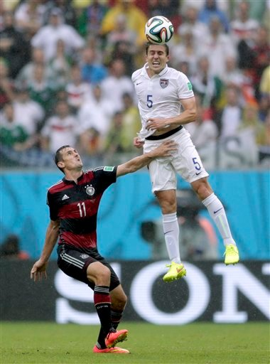 United States' Matt Besler goes up to head the ball over Germany's Miroslav Klose during the group G World Cup soccer match between the United States and Germany at the Arena Pernambuco in Recife, Brazil, Thursday, June 26, 2014.