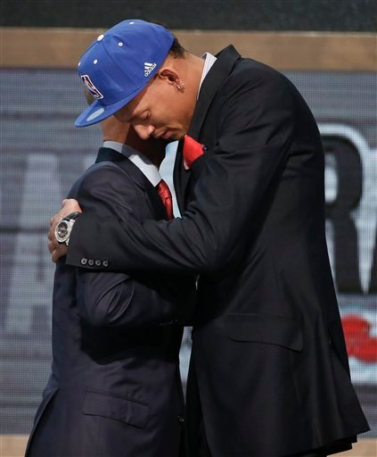 Baylor center Isaiah Austin, right, hugs NBA Commissioner Adam Silver after being granted ceremonial first round pick during the 2014 NBA draft, Thursday, June 26, 2014, in New York.