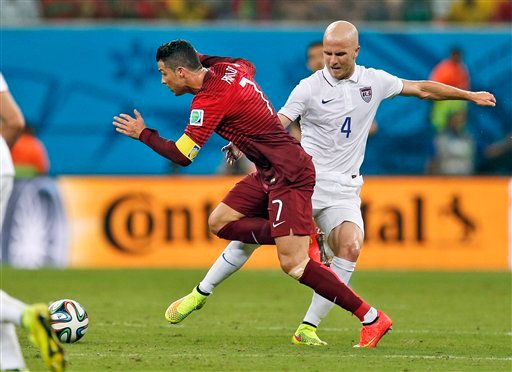 Portugal's Cristiano Ronaldo is tripped up by United States' Michael Bradley during the group G World Cup soccer match between the United States and Portugal at the Arena da Amazonia in Manaus, Brazil, Sunday, June 22, 2014. (AP Photo/Julio Cortez)