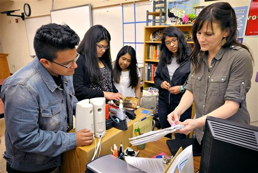 This May 28, 2014, file photo shows teacher Amanda Filloy Sharp, right, reviewing potluck items with her students, from left Diego Munoz, Stephanie Vidrio, Thania Lopez and Cynthia Cruz, at the end of class in Corvallis, Ore.