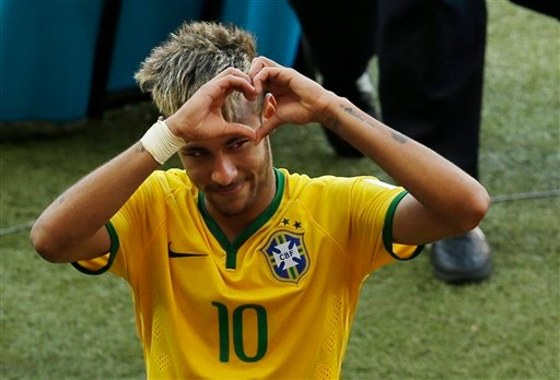 Brazil's Neymar forms a heart with his hands as he leaves the pitch after the World Cup round of 16 soccer match between Brazil and Chile at the Mineirao Stadium in Belo Horizonte, Brazil, Saturday, June 28, 2014.