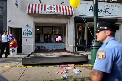 Investigators look over the debris of a fallen security door outside a Rita's Water Ice store in the Brewerytown section of Philadelphia on Saturday, June 28, 2014.
