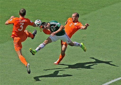 Mexico's Hector Herrera, center, challenges for the ball with Netherlands' Stefan de Vrij, left, and Ron Vlaar during the World Cup round of 16 soccer match between the Netherlands and Mexico at the Arena Castelao in Fortaleza, Brazil, Sunday, June 29.