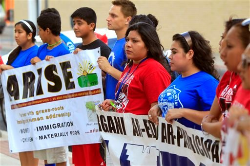 Immigrant advocates attend a vigil to show support for the refugee children and families arriving in the Rio Grande Valley and to draw attention to the causes and solutions to the refugee crisis Friday, June 27, 2014.