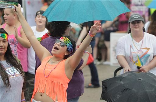 People listen to music while it rains during the Houston Pride Festival on Saturday, June 28, 2014, in Houston. (AP Photo/Houston Chronicle, Mayra Beltran)