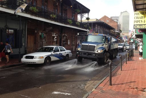 A Progressive Waste Solutions truck sprays along Bourbon Street, following a shooting earlier in the day, Sunday, June 29, 2014, in New Orleans.