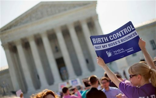 A demonstrator holds up a sign outside the Supreme Court in Washington, Monday, June 30, 2014.