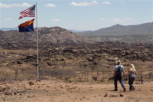 This Aug. 9, 2013 file photo shows David and Shari Turbyfill walking to the memorial flag at the site where their son Travis Turbyfill was killed during the Yarnell Fire.