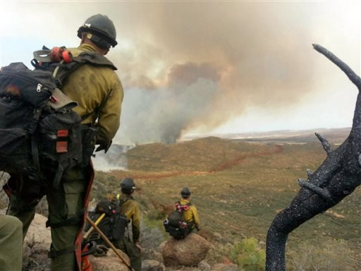 In this Sunday, June 30, 2013 file photo made by firefighter Andrew Ashcraft, members of the Granite Mountain Hotshots watch a growing wildfire that later swept over and killed the crew of 19 firefighters near Yarnell, Ariz.