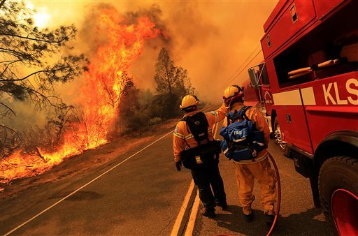 Kelseyville firefighters prepare to pull back from the fire on Butts Canyon Road, as the fire jumps the road July, 1, 2014, outside Middletown, Calif., at the border between Lake and Napa counties. (AP Photo/The Press Democrat, Kent Porter)