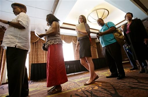 In this Thursday, June 12, 2014 photo, people wait in line for the Cleveland Career Fair in Independence, Ohio. (AP Photo/Tony Dejak)