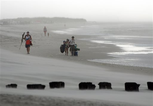 Clouds and rains move in as beachgoers leave Freeman Park at the north end of Carolina Beach, N.C., Thursday, July 3, 2014. (AP Photo/Wilmington Star-News, Mike Spencer)