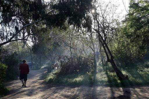 In this March 18, 2014 photo, man walks along a pathway in the early morning in the Jungle, a homeless encampment in San Jose, Calif.