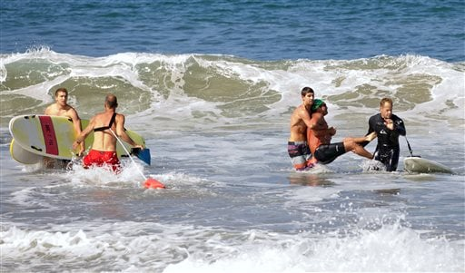 In this photo by Laura Joyce of goofyfootphotography.com, two men carry a swimmer, second from right, after he was bitten by a great white shark, as lifeguards close in at left in the ocean off Southern California's Manhattan Beach, Saturday, July 5, 2014
