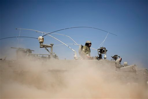 Israeli soldiers drive on an armored personal carrier near the Israel and Gaza Strip border, Monday, July 7, 2014.
