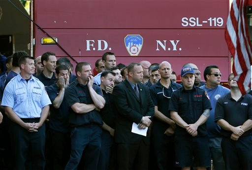 Firefighters watch as other firefighters hang bunting over the firehouse in honor of Lt. Gordon Ambelas in New York, Sunday, July 6, 2014.