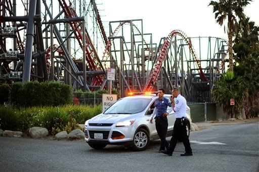 Members of the Six Flags Magic Mountain amusement park security staff monitor the situation at the exit of the park after riders were injured on the Ninja coaster Monday, July 7, 2014, in Valencia, Calif.
