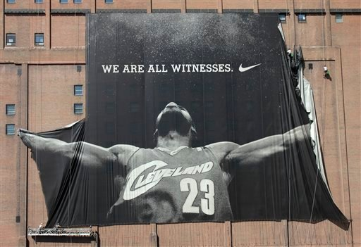 In this July 11, 2010 file photo, A 10-story banner of former Cleveland Cavaliers NBA basketball star LeBron James is taken down by workers in downtown Cleveland, Ohio.
