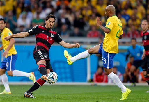 Germany's Mats Hummels, left, and Brazil's Maicon challenge for a ball during the World Cup semifinal soccer match between Brazil and Germany at the Mineirao Stadium in Belo Horizonte, Brazil, Tuesday, July 8, 2014. (AP Photo/Frank Augstein)