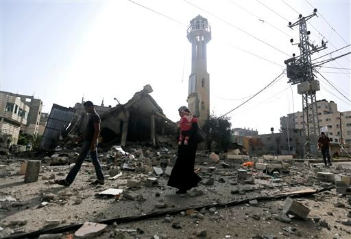 Palestinians walk past the ruins of the Al-Tawfeeq mosque after it was hit by an Israeli missile strike in the Nuseirat refugee camp, central Gaza Strip, Saturday, July 12, 2014.