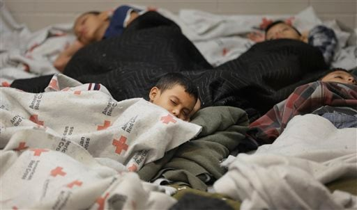 This June 18, 2014, file photo, detainees sleep in a holding cell at a U.S. Customs and Border Protection, processing facility in Brownsville,Texas.