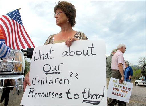Protester Deborah Pfaff stands near the entrance to juvenile facility in an effort to stop a bus load of Central American immigrant children from being delivered to the facility, Tuesday, July 15, 2014, in Oracle, Ariz. (AP)