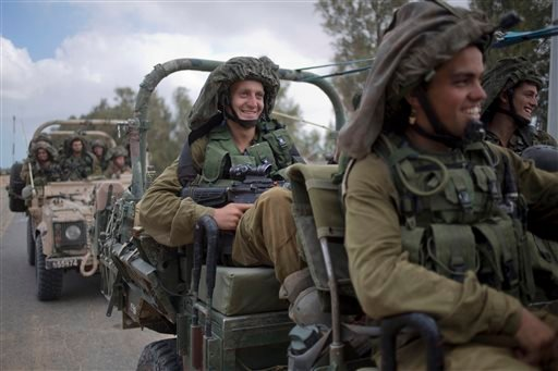 Israeli soldiers smile as they ride on a military vehicle near the Israel-Gaza Border, Thursday, July 17, 2014.
