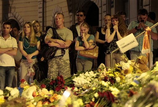 People stand near flower tributes placed outside the Dutch embassy to commemorate victims of Malaysia Airlines plane crash in Kiev, Ukraine, Thursday, July 17, 2014. (AP)