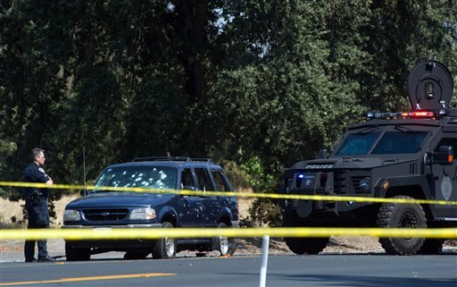 A Stockton Police officer investigates the scene after a vehicle involved in a suspected bank robbery was stopped on Wednesday, July 16, 2014, in Stockton, Calif.