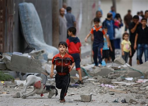 A Palestinian child runs on debris from a destroyed house, following an overnight Israeli strike in Beit Lahiya, in northern Gaza strip, Saturday, July 19, 2014.