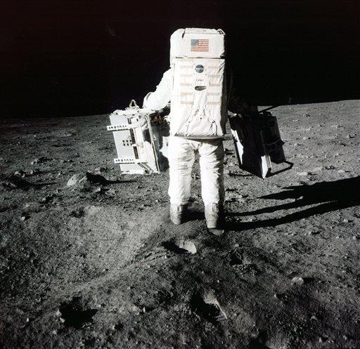 "In this July 20, 1969 file photo provided by NASA, Edwin ""Buzz"" Aldrin carries scientific experiments to a deployment site south of the lunar module Eagle during the Apollo 11 mission."
