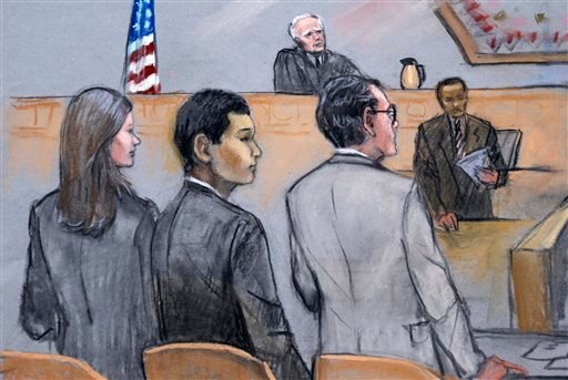In this courtroom sketch, defendant Azamat Tazhayakov, foreground center, a college friend of Boston Marathon bombing suspect Dzhokhar Tsarnaev, is stands between his attorneys as the verdict is read in his federal trial, Monday, July 21, 2014 in Boston.
