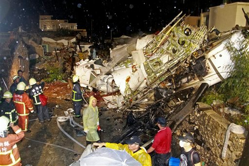 Rescue workers work next to the wreckage of TransAsia Airways flight GE222 which crashed while attempting to land in stormy weather on the Taiwanese island of Penghu July 23, 2014. (AP Photo/Wong Yao-wen)