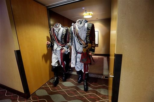 In this July 19, 2013 file photo, two men dressed as headless characters get off a hotel elevator in San Digeo. Like Batman responding to a beaming Bat signal in the sky, pop-culture fans are flocking to San Diego for the 45th annual Comic-Con.