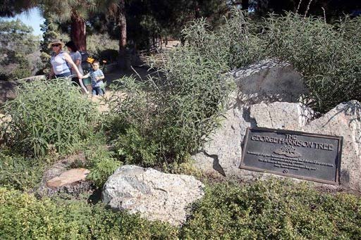Visitors walk past a plaque marking the George Harrison Tree, in Griffith Park on Tuesday, July 22, 2014.