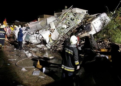 Rescue workers survey the wreckage of TransAsia Airways flight GE222 which crashed while attempting to land in stormy weather on the Taiwanese island of Penghu, late Wednesday, July 23, 2014. (AP)