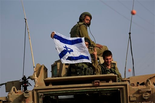Israeli soldiers display national flag on top of an armored personnel carrier near the border of Israel and Gaza Strip Wednesday, July 23, 2014. (AP)