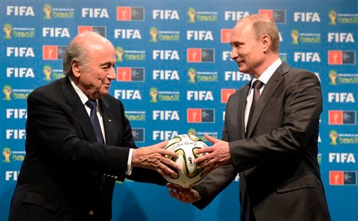 In this file photo taken on Sunday, July 13, 2014, FIFA President Sepp Blatter, left, and Russian President Vladimir Putin hold a soccer ball during the official ceremony of handover to Russia as the 2018 World Cup hosts.