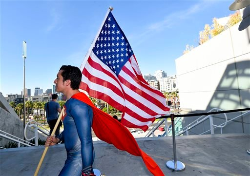 Bersain Gutierrez, dressed as Superman, carries an American flag during preview night at the 2014 Comic-Con International Convention held Wednesday, July 23, 2014 in San Diego. (Photo by Denis Poroy/Invision/AP)