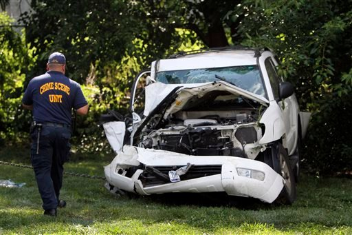 An investigator examines a heavily damaged SUV before it is towed from the scene of a fatal accident in North Philadelphia, Friday July 25, 2014.